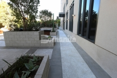 Bomanite Revealed Exposed Aggregate decorative concrete was installed here to create walkways, paths, and an outdoor entertaining area with an elegant finish that complements the design and architectural features of the adjacent building.