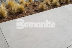 The hardscape featured here was created using Bomanite Sandscape Refined decorative concrete and the use of white color hardener paired with locally sourced aggregates, mirror glass, and distinctive saw cuts creates an aesthetic that matches the nautical themed design at the 50 Fifty DTC office complex.