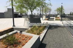 Featured here is a gray Bomanite Exposed Aggregate Sandscape Texture finish that was added to these lineal planters and circular tree planters to add textural detail that complements the geometrical arrangement of the pedestal pavers on this rooftop terrace and garden.