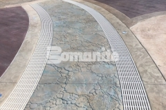 This meandering brook hardscape at Canobie Lake Park was created using Bomanite Imprint Systems and was expertly installed by our colleague, Harrington Bomanite, to include these serpentine drains that can infiltrate storm water and minimize runoff while accentuating the decorative concrete decking at the Castaway Island water feature.
