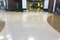 Featured here is Bomanite Modena Monolithic decorative concrete flooring in a Snow White color that was mixed with Cool Gray to provide tone and was hand-seeded with mirrored glass, sea shells, and mother of pearl to create a shimmering effect that emulates shells and sea glass in the sun.