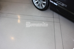 This finished floor is made up of white-base Bomanite Modena SL with accent areas of a black Bomanite Modena SL and decorative zinc terrazzo that was polished to provide a low maintenance, showroom caliber concrete.