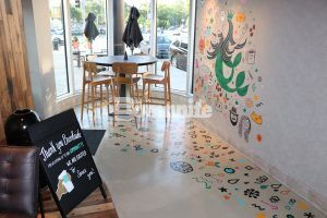 Starbucks design team featured artwork on wall and decorative concrete flooring installed at the Brookside Kansas City store by Musselman & Hall using Bomanite Custom Polishing System with Modena SL.