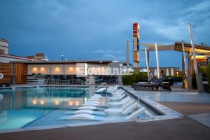 Wide view with lounge chairs in the pool at the Hard Rock Casino in Tulsa, OK, featuring Bomanite Exposed Aggregate Alloy decorative concrete installed by Bomanite of Tulsa.